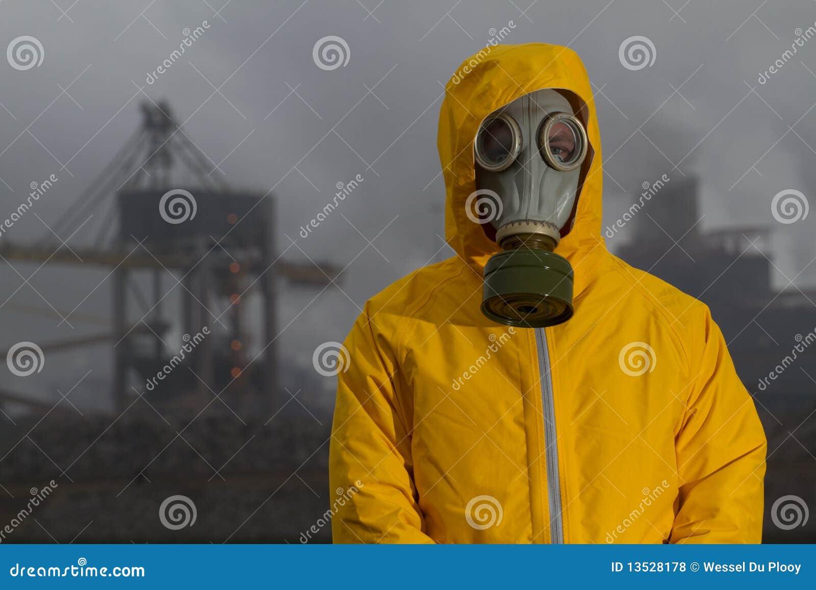 Equipe o infront ereto desgastando da máscara de gás da fábrica.