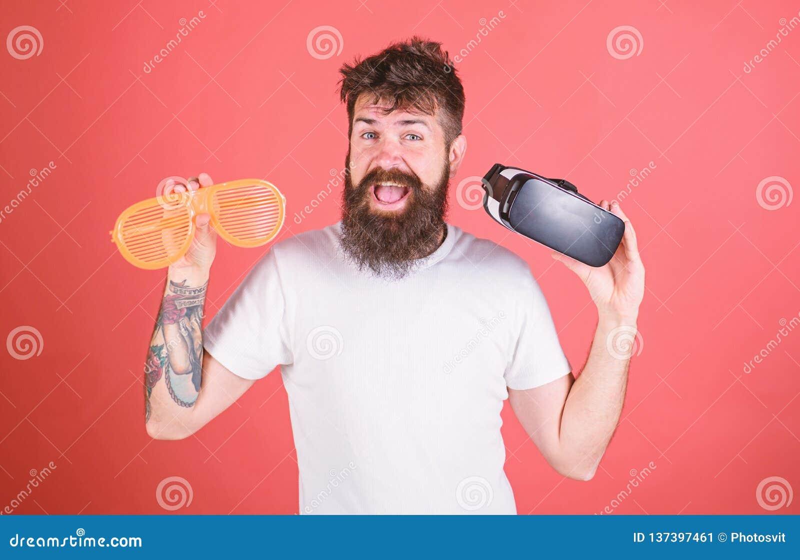 Equipe o moderno farpado com os auriculares da realidade virtual e os óculos de sol louvered no fundo vermelho Homem que faz a de