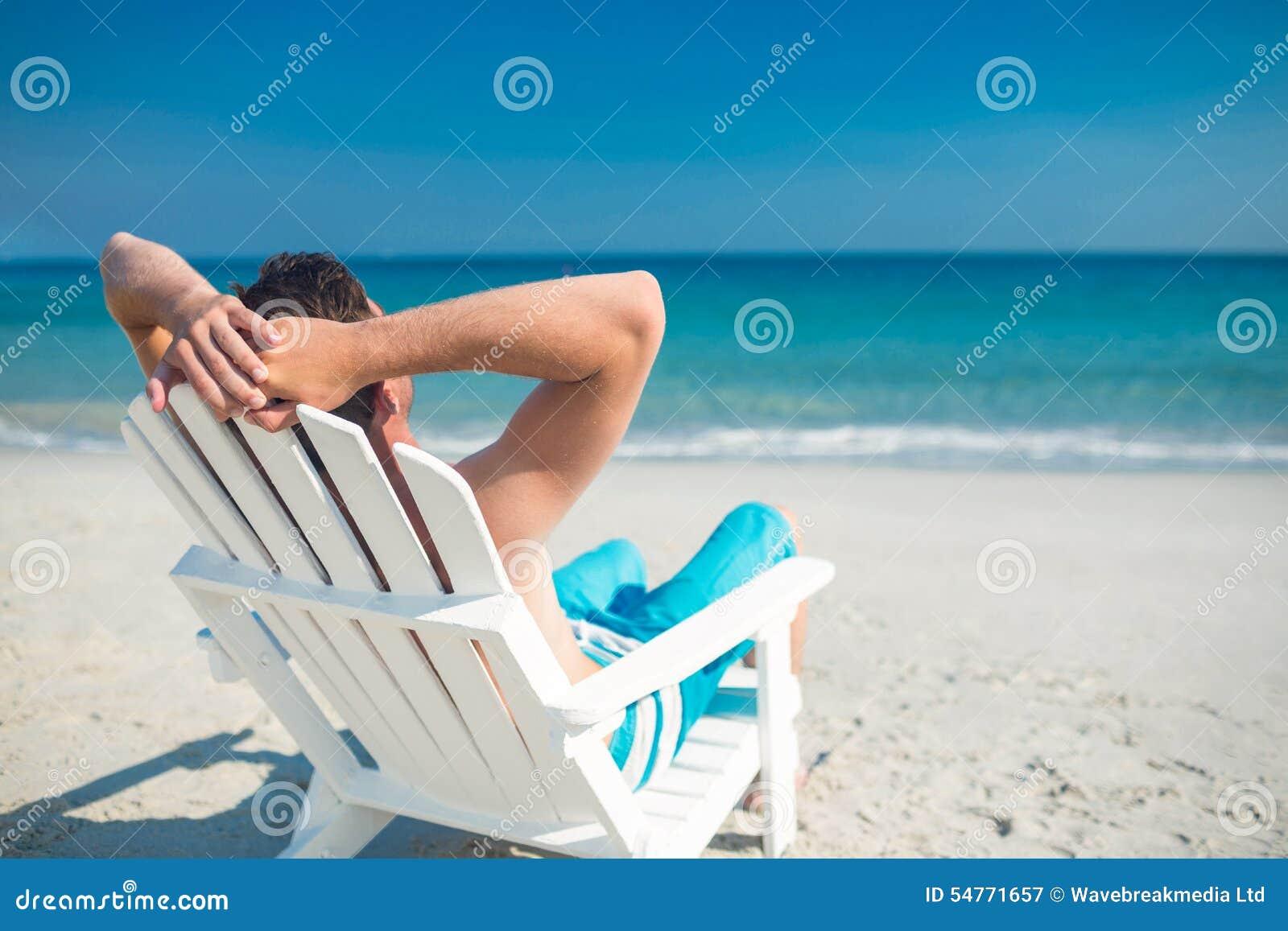 Equipe o relaxamento na cadeira de plataforma na praia