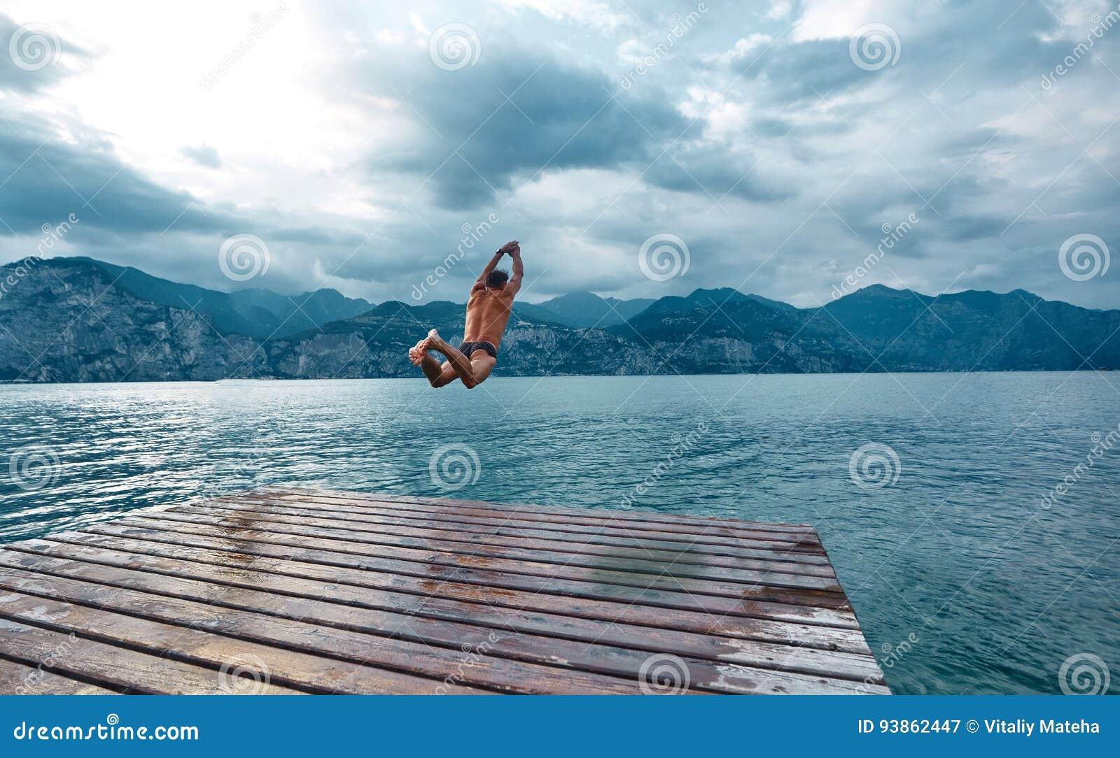 Equipe o salto na água do cais