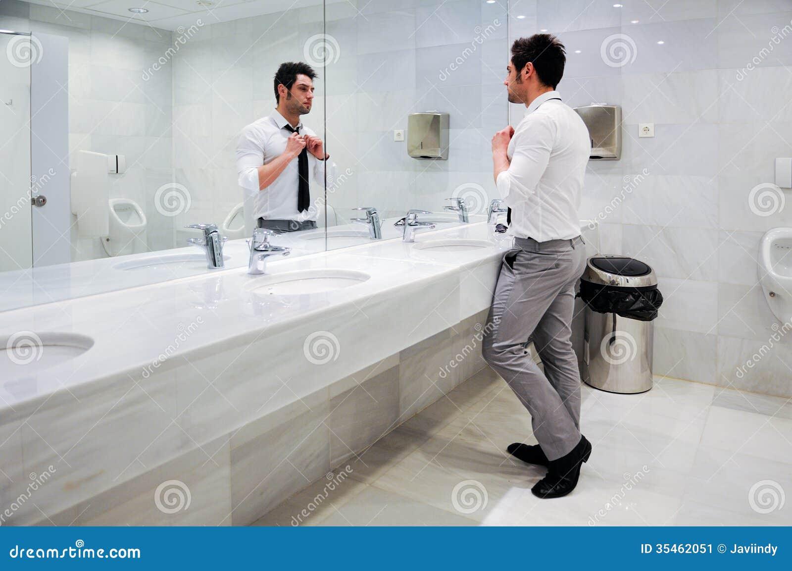 Equipe a obtenção vestido em um toalete público com espelho