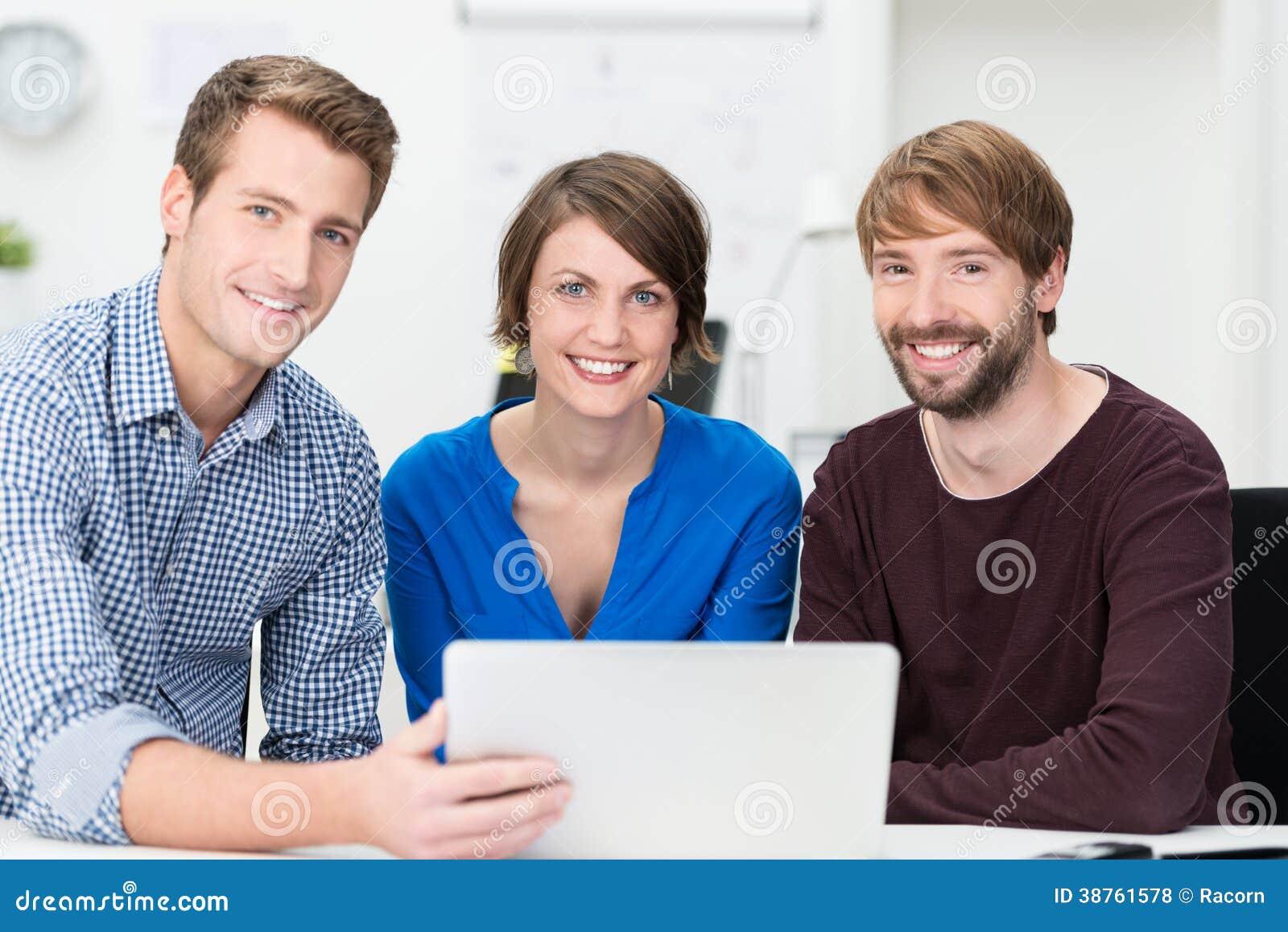 Equipe segura do negócio agrupada em torno de um portátil
