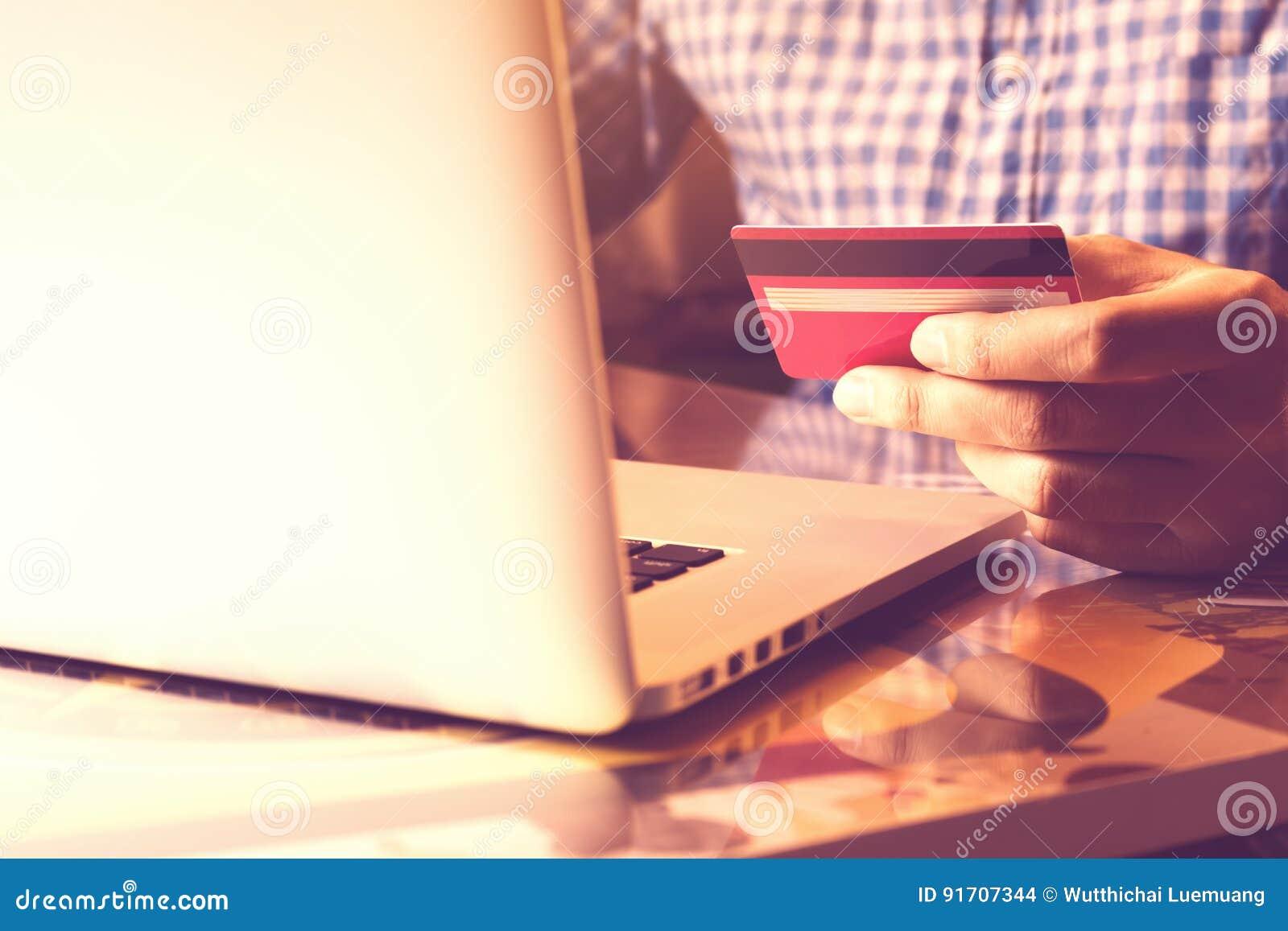 Equipe usando o portátil e guardando o cartão de crédito com conceito em linha da compra ou dos Internet banking