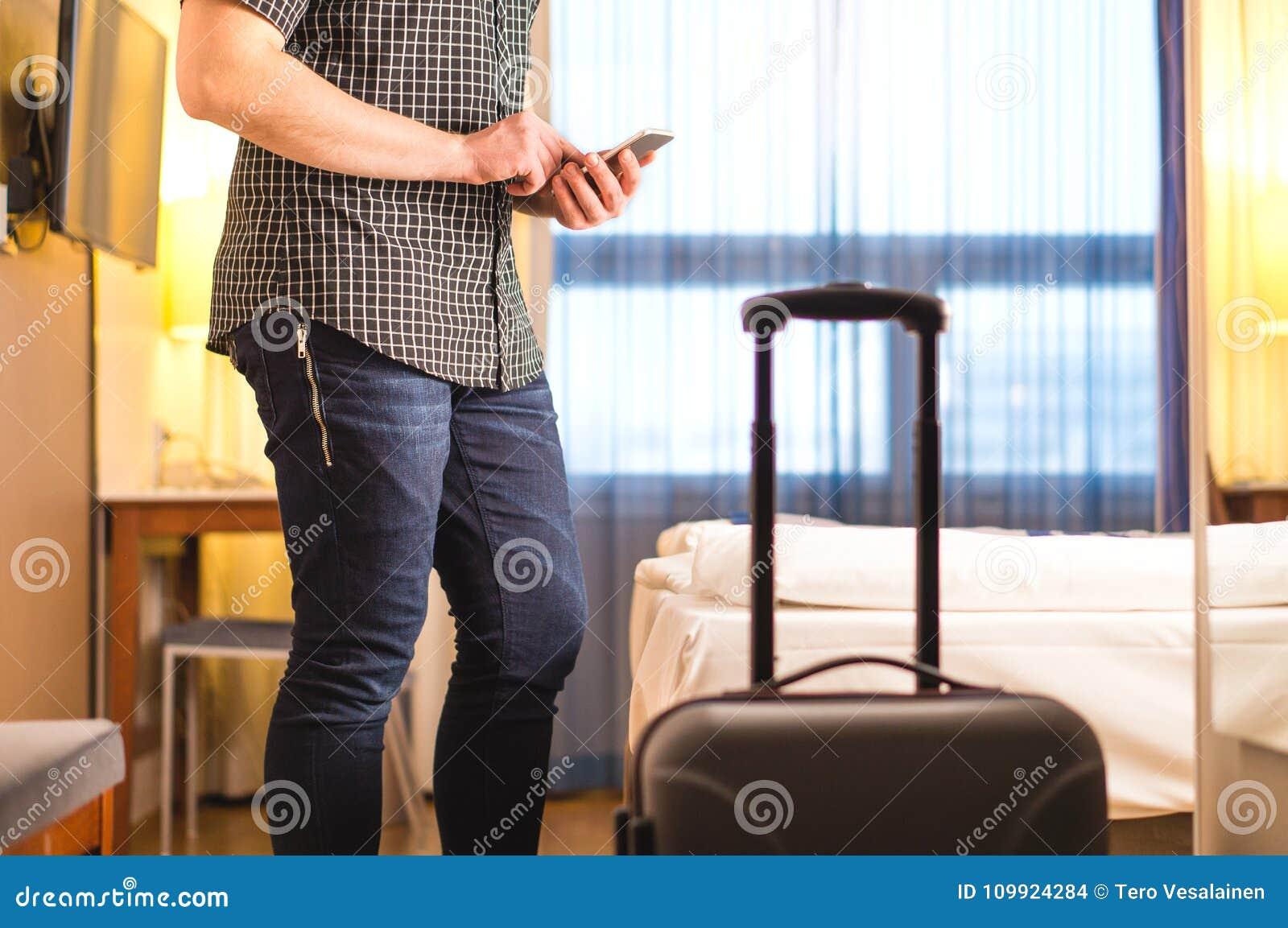 Equipe usando o smartphone na sala de hotel com bagagem e mala de viagem