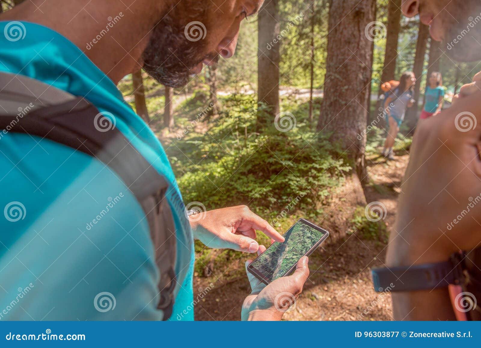 Equipe a verificação de gps do smartphone traçam no trajeto da fuga de caminhada na floresta w