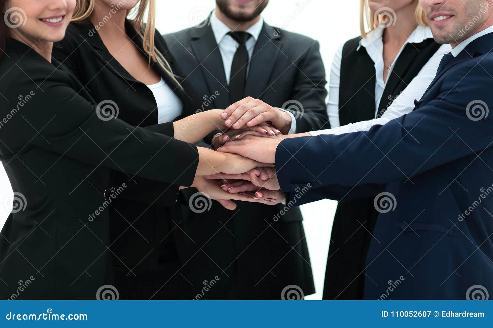 Equipo amistoso del negocio con las manos abrochadas juntas