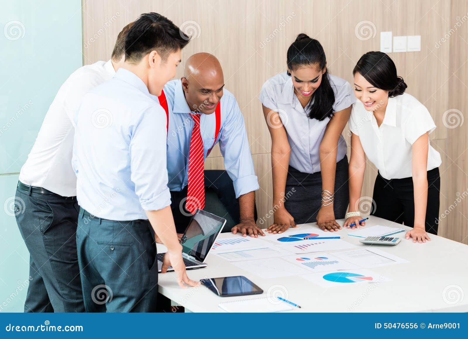 Equipo asiático de la puesta en marcha del negocio en la reunión