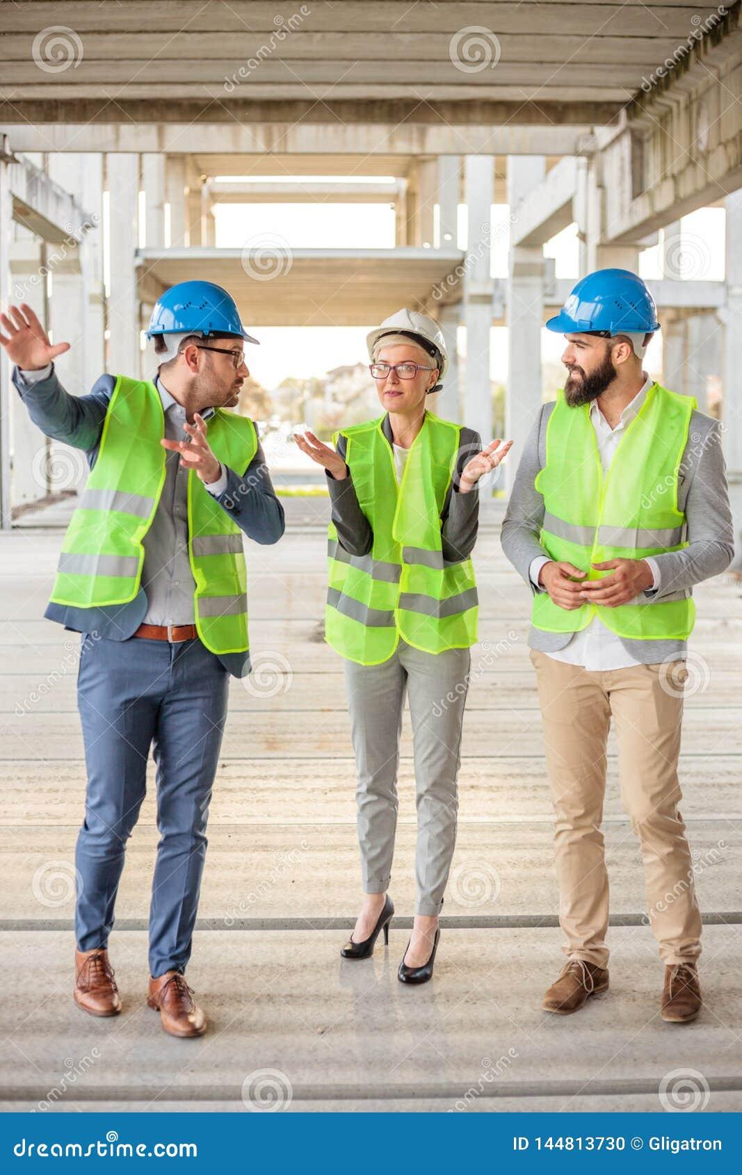 Equipo de arquitectos acertados y de socios comerciales que toman un viaje del emplazamiento de la obra