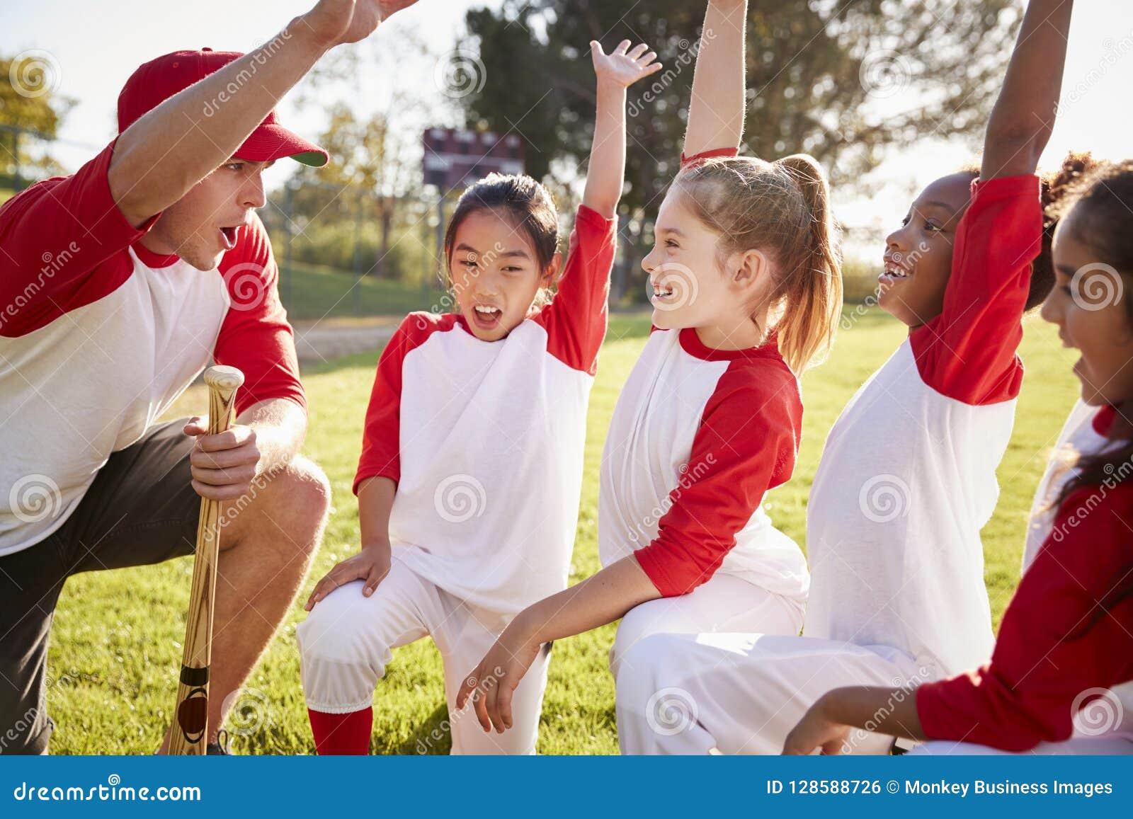 Equipo de béisbol de la muchacha que se arrodilla con su entrenador, aumentando las manos