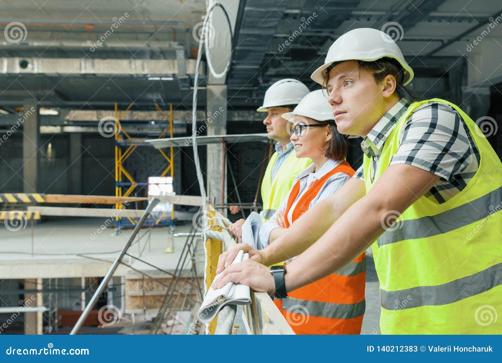 Equipo de constructores, ingenieros, arquitectos en el emplazamiento de la obra, espacio de la copia Concepto de la construcción,