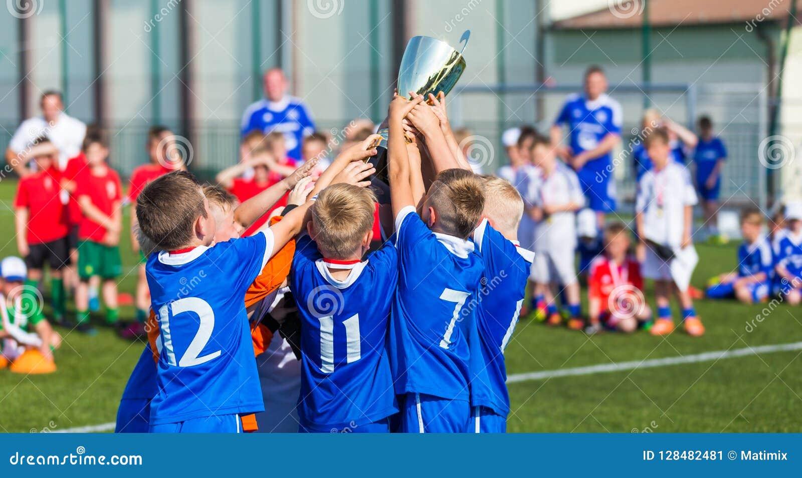 Equipo de deporte joven con el trofeo Muchachos que celebran los deportes Achievemen