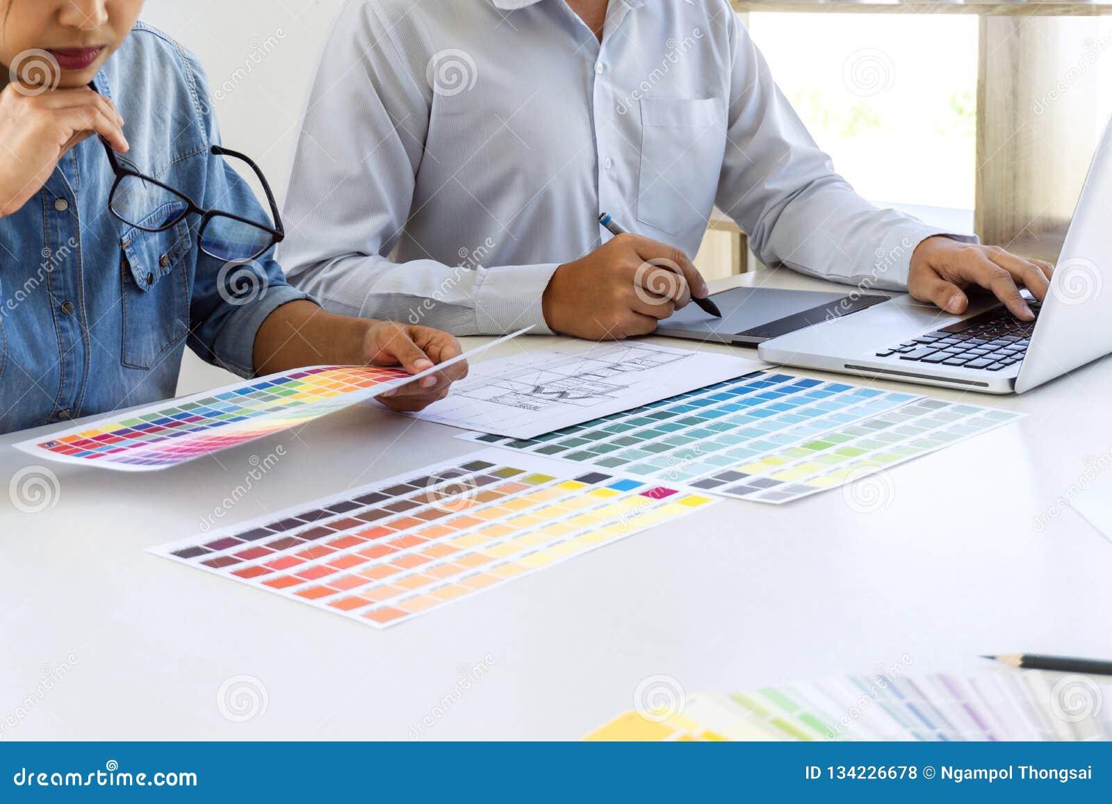 Equipo de dibujo del diseñador gráfico del colega y de imagen que retoca en la tableta de gráficos y elegir las muestras de la mu