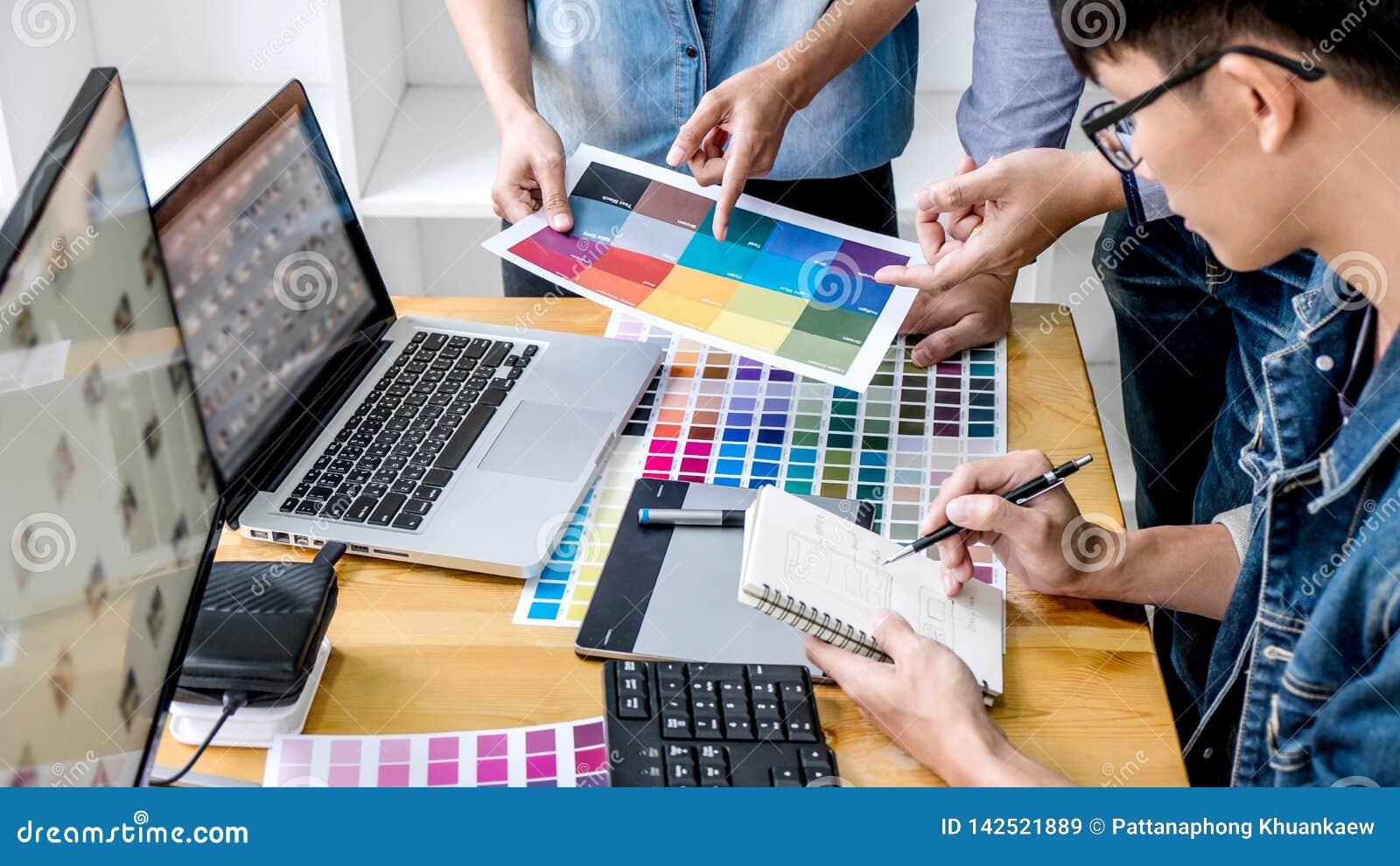 Equipo de diseñador gráfico creativo de los colegas jovenes que trabaja en la selección de color y que dibuja en la tableta de gr