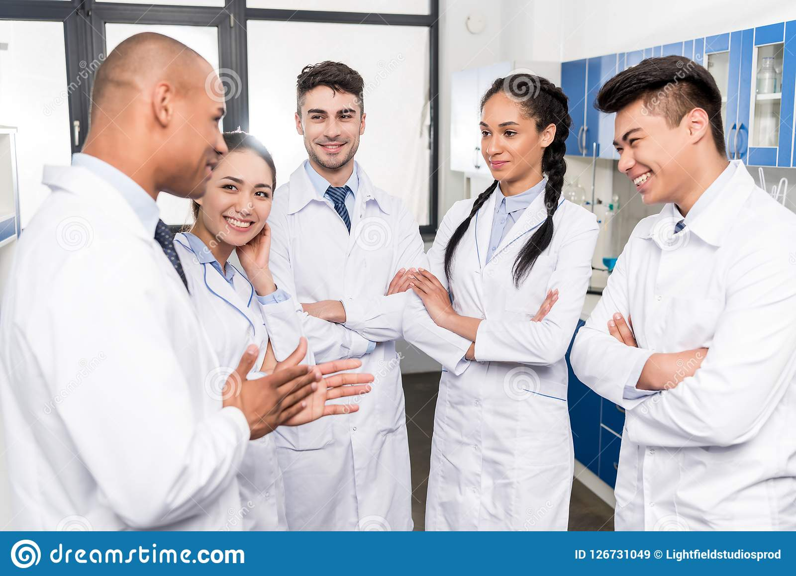 Equipo de doctores jovenes en capas del laboratorio que discuten el trabajo