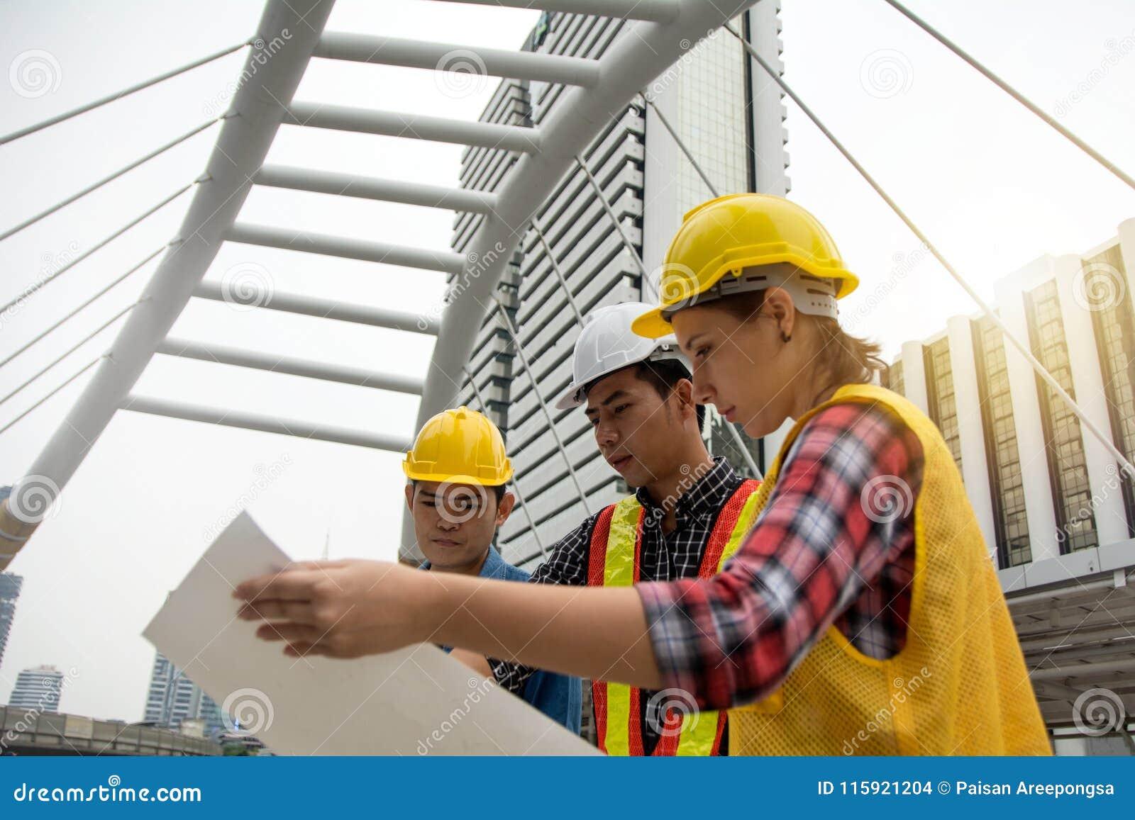 Equipo de hembras jovenes y de ingenieros de sexo masculino que trabajan en la construcción favorable