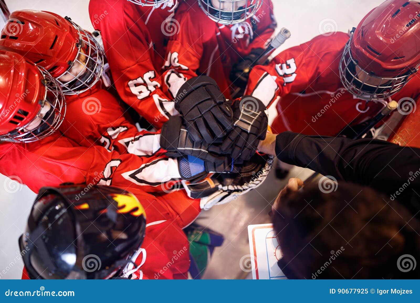 Equipo de hockey que trabaja en trabajo en equipo del triunfo junto