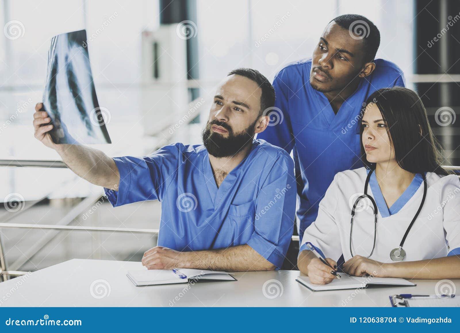 Equipo de hospital de los doctores Examining X-ray Scan In