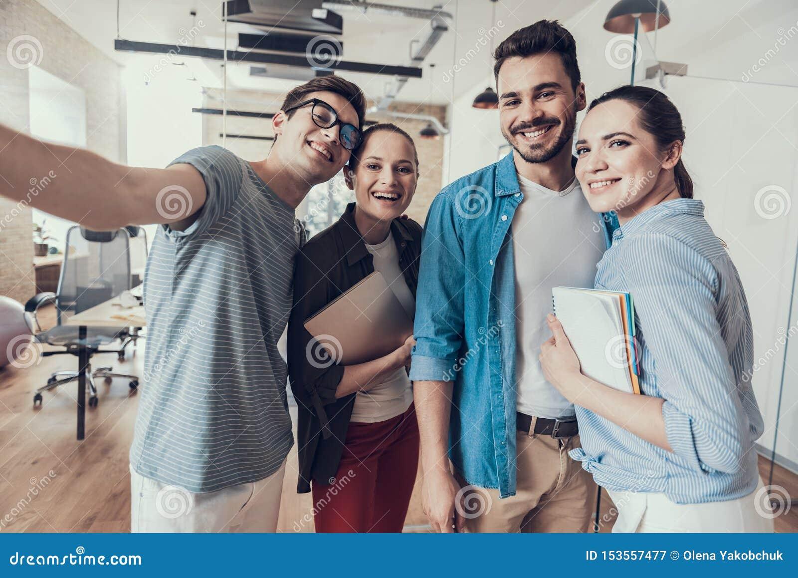 Equipo de lanzamiento joven feliz que permanece en sala de reunión