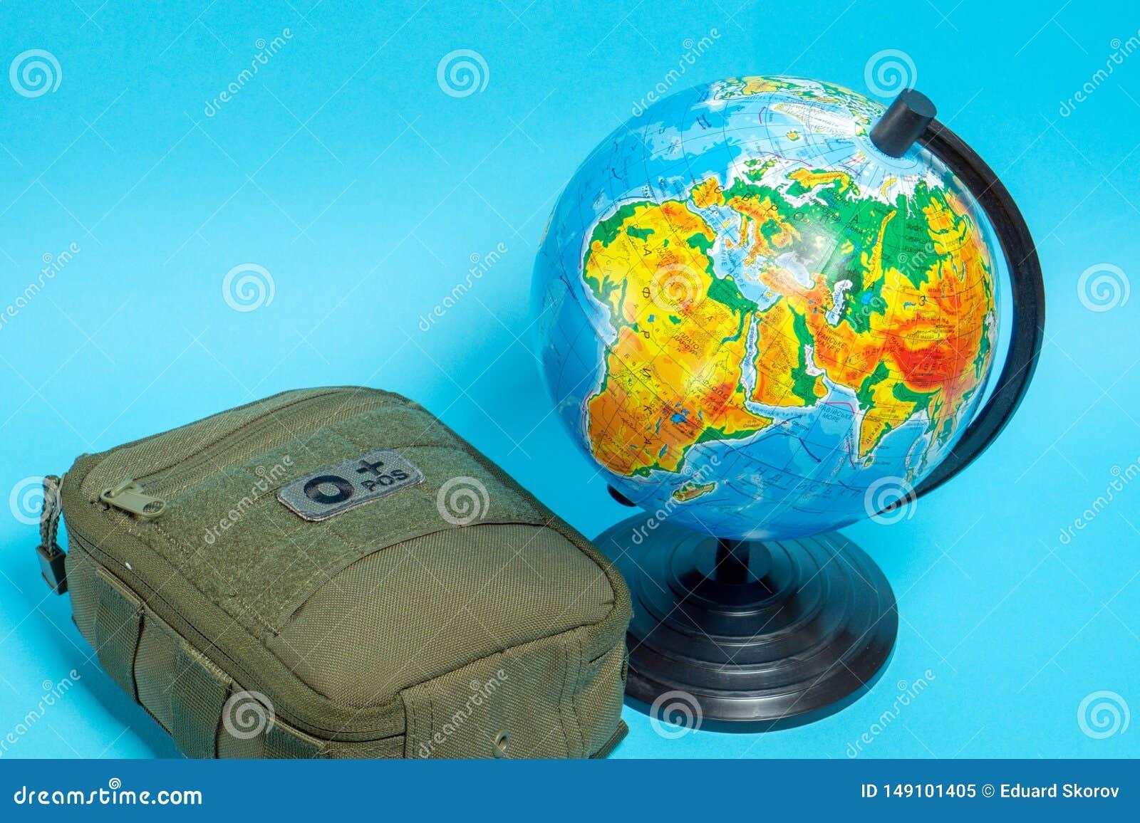 Equipo de primeros auxilios verde al lado del globo en un fondo azul