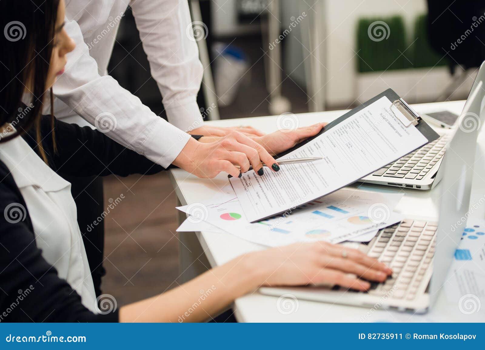 Equipo del negocio que analiza gráficos de la renta con los ordenadores portátiles modernos Ciérrese encima de concepto del análi