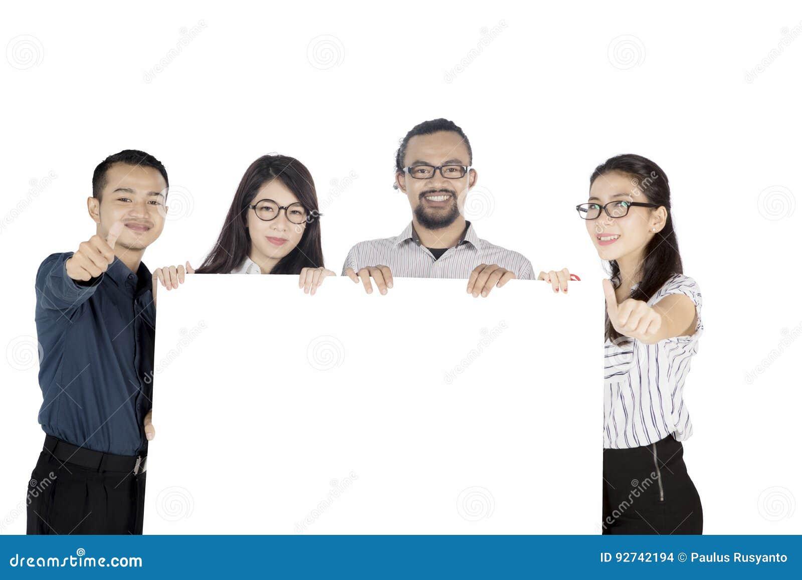 Equipo del negocio que muestra los pulgares para arriba en la cámara
