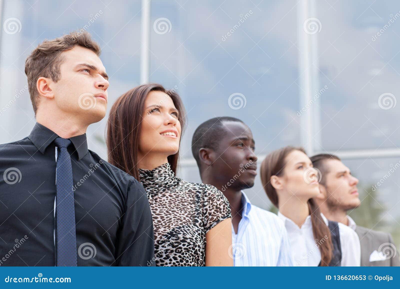 Equipo del negocio que se coloca en fila en la oficina y que mira hacia arriba - al equipo acertado del negocio