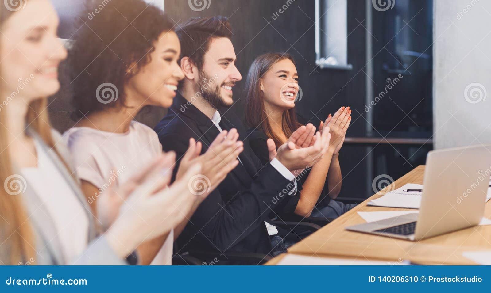 Equipo diverso feliz del negocio que aplaude en la conferencia