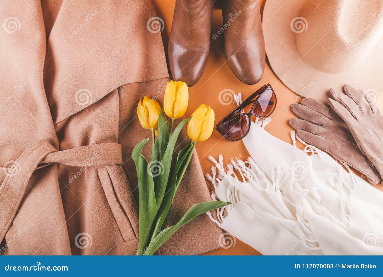 Equipo femenino de la primavera con los tulipanes amarillos Sistema de ropa, de zapatos y de accesorios en fondo anaranjado