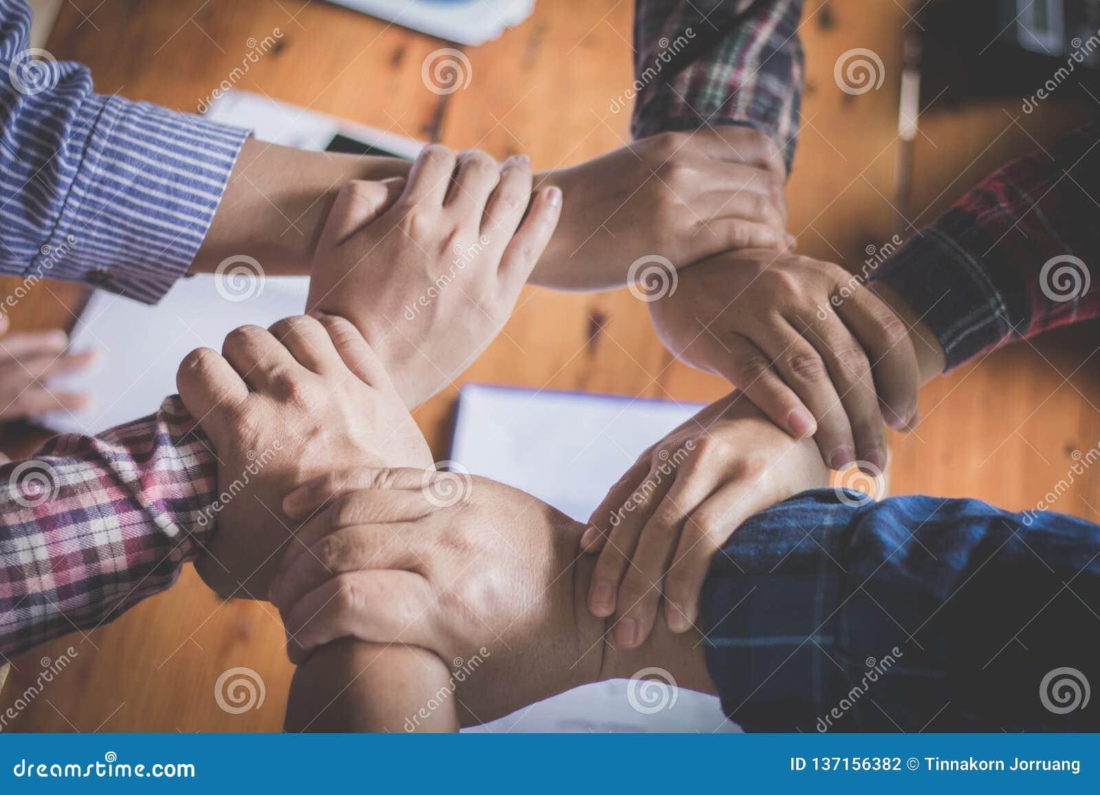 Equipo joven que pone las manos para el nuevo inicio en oficina creativa, el Co-trabajo de Team Teamwork Togetherness Collaborati