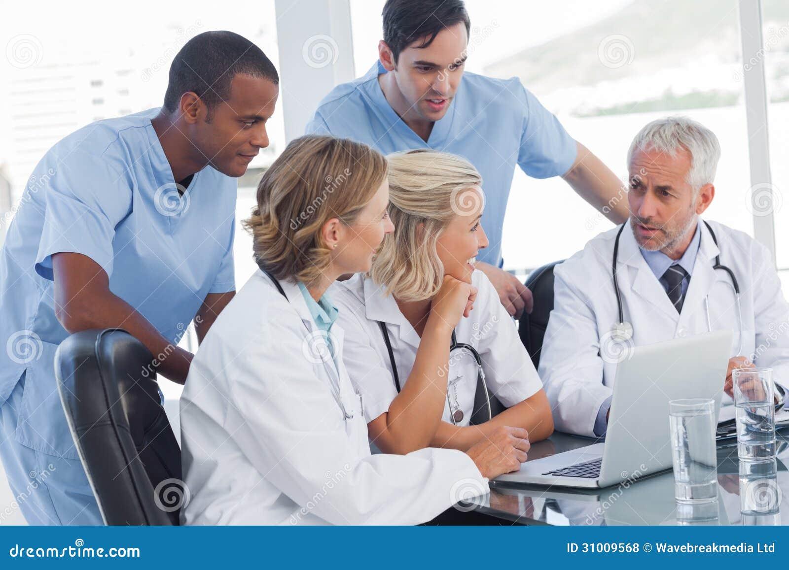 Equipo médico sonriente usando el ordenador portátil