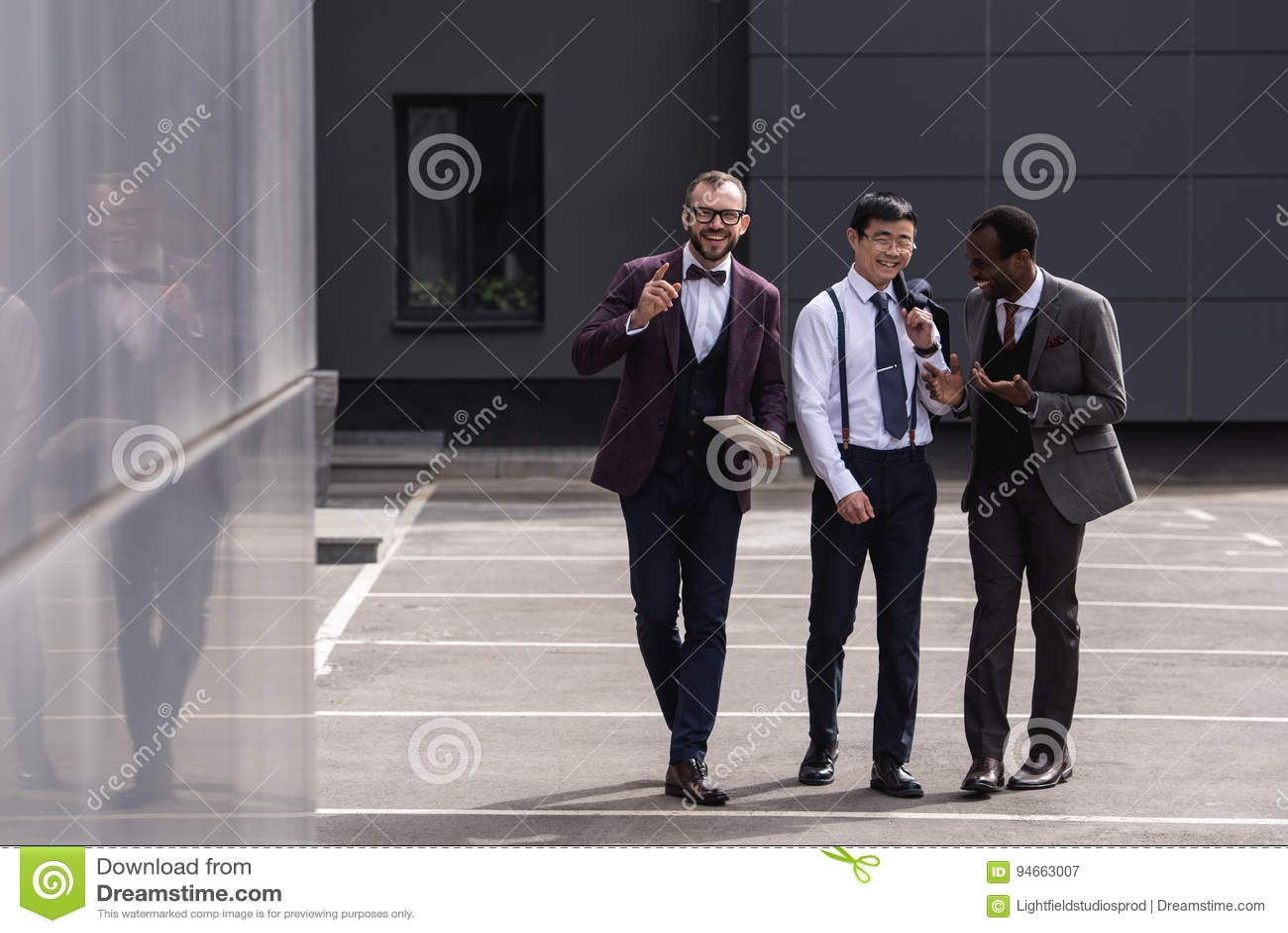 Equipo multicultural del negocio que camina en la calle cerca del edificio de oficinas moderno