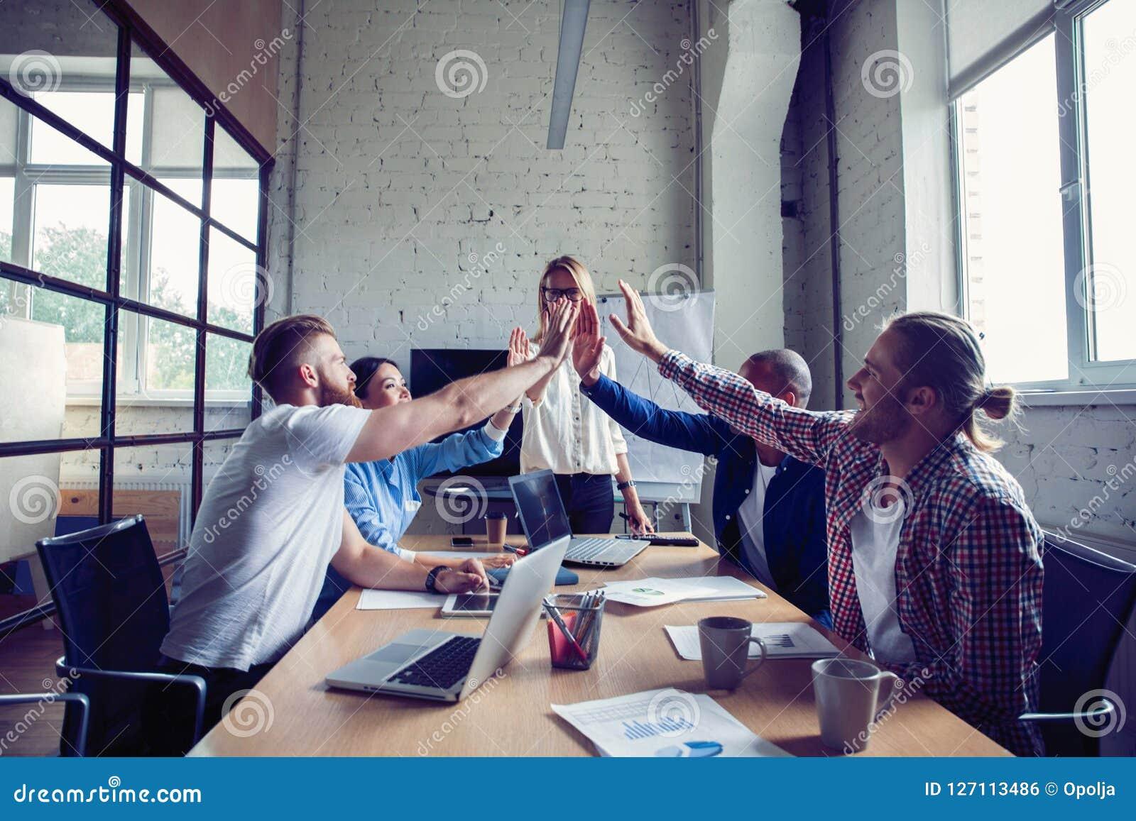 Equipo multirracial acertado feliz del negocio que da un gesto de los fives del alto como él ríe y anima su éxito