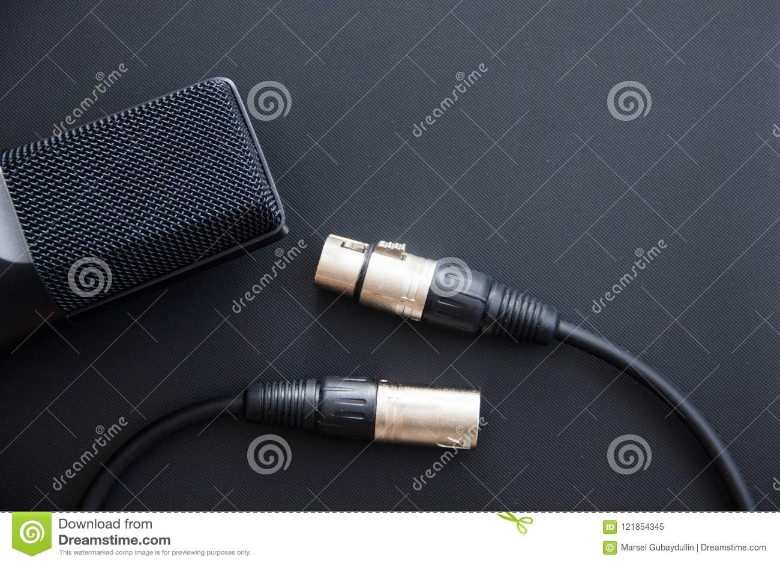 Equipo musical, micrófono profesional del estudio del condensador con el cable del xlr, color oscuro Ciérrese para arriba desde a