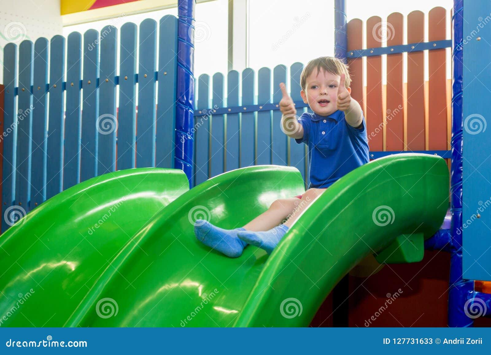 Equitação da criança das corrediças das crianças no centro de jogo e nos polegares das mostras acima Criança feliz, crianças que