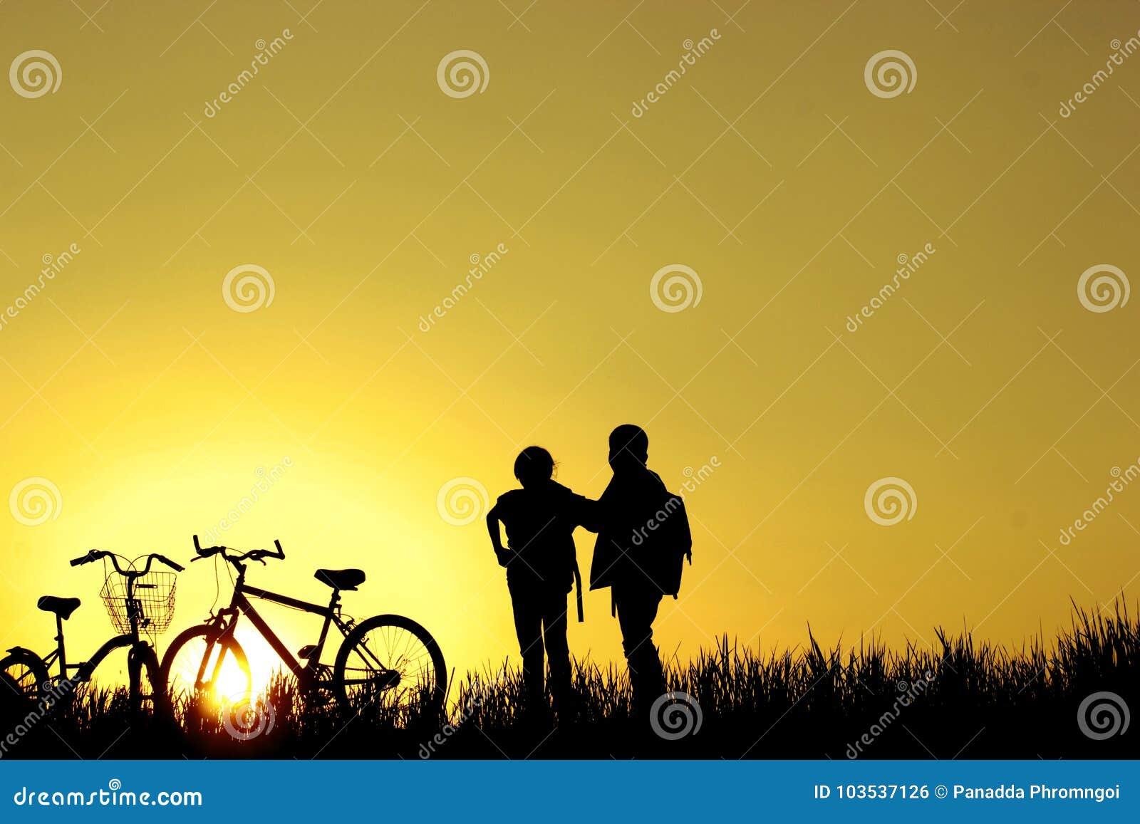 A equitação do rapaz pequeno e da menina bikes no por do sol, crianças ativas ostenta, criança asiática, mostra em silhueta uma c