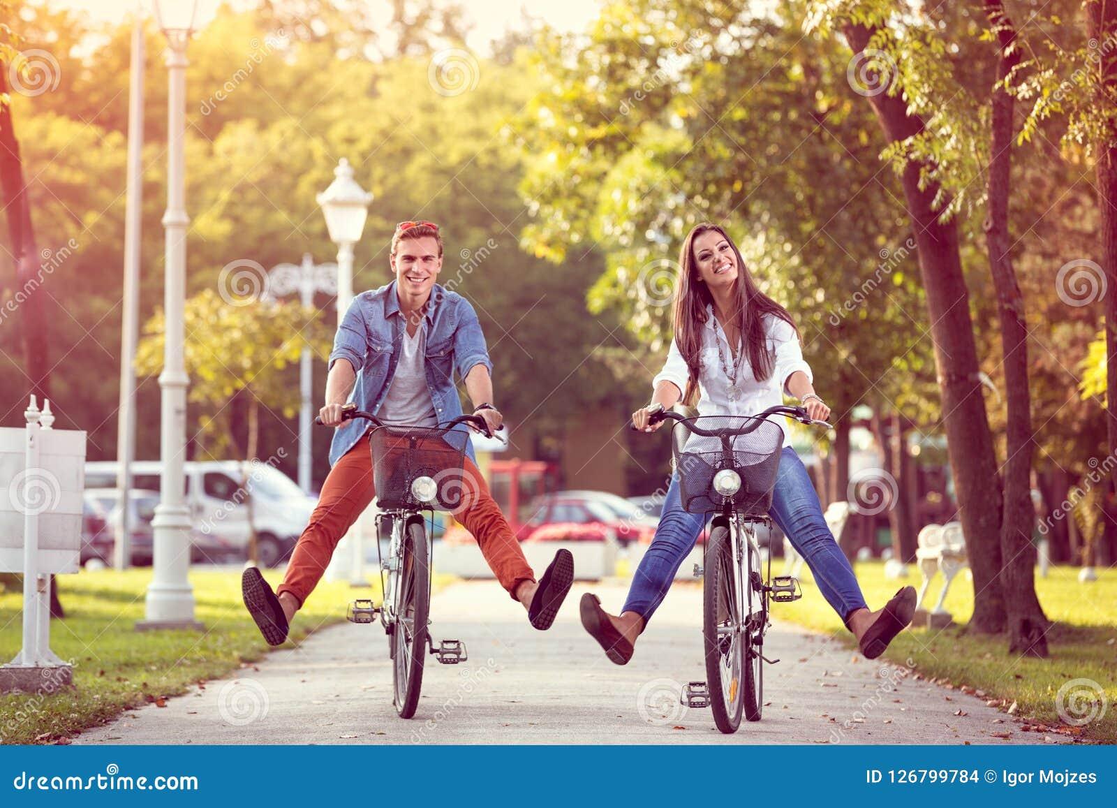 Equitação engraçada dos pares do outono feliz na bicicleta