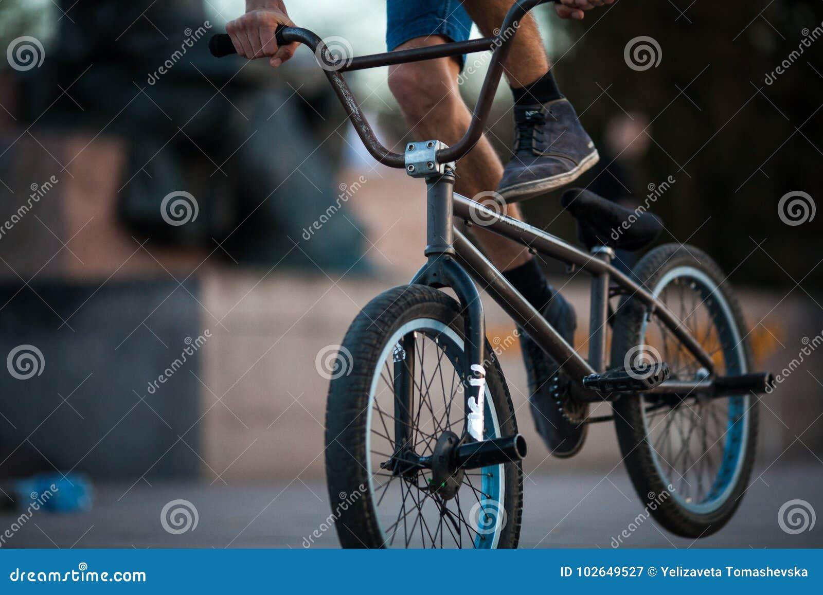 Equitação nova do menino do ciclista do adolescente no backgro masculino do close up da parte mais inferior do passatempo do espo