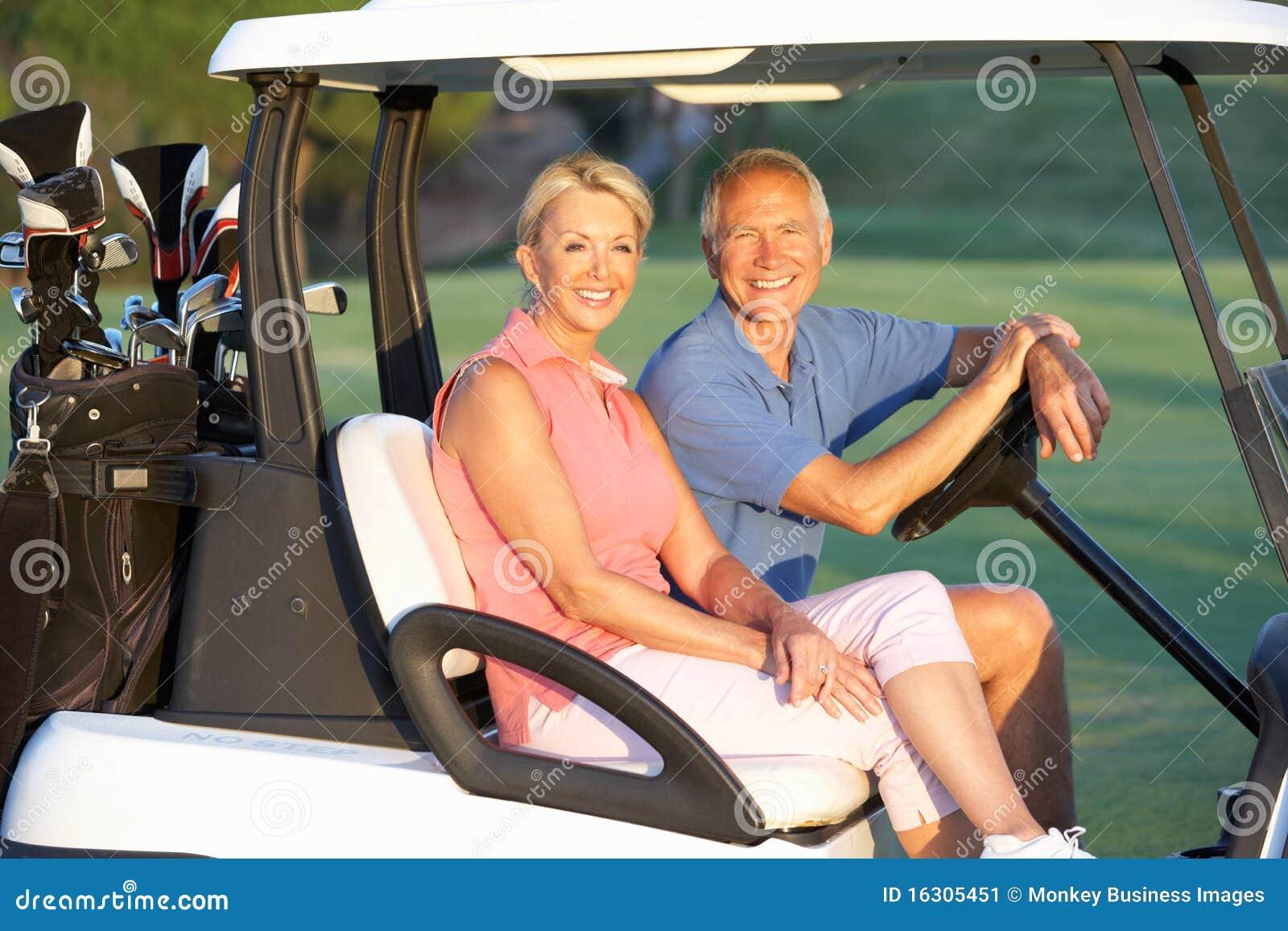 Equitação sênior dos pares no Buggy do golfe
