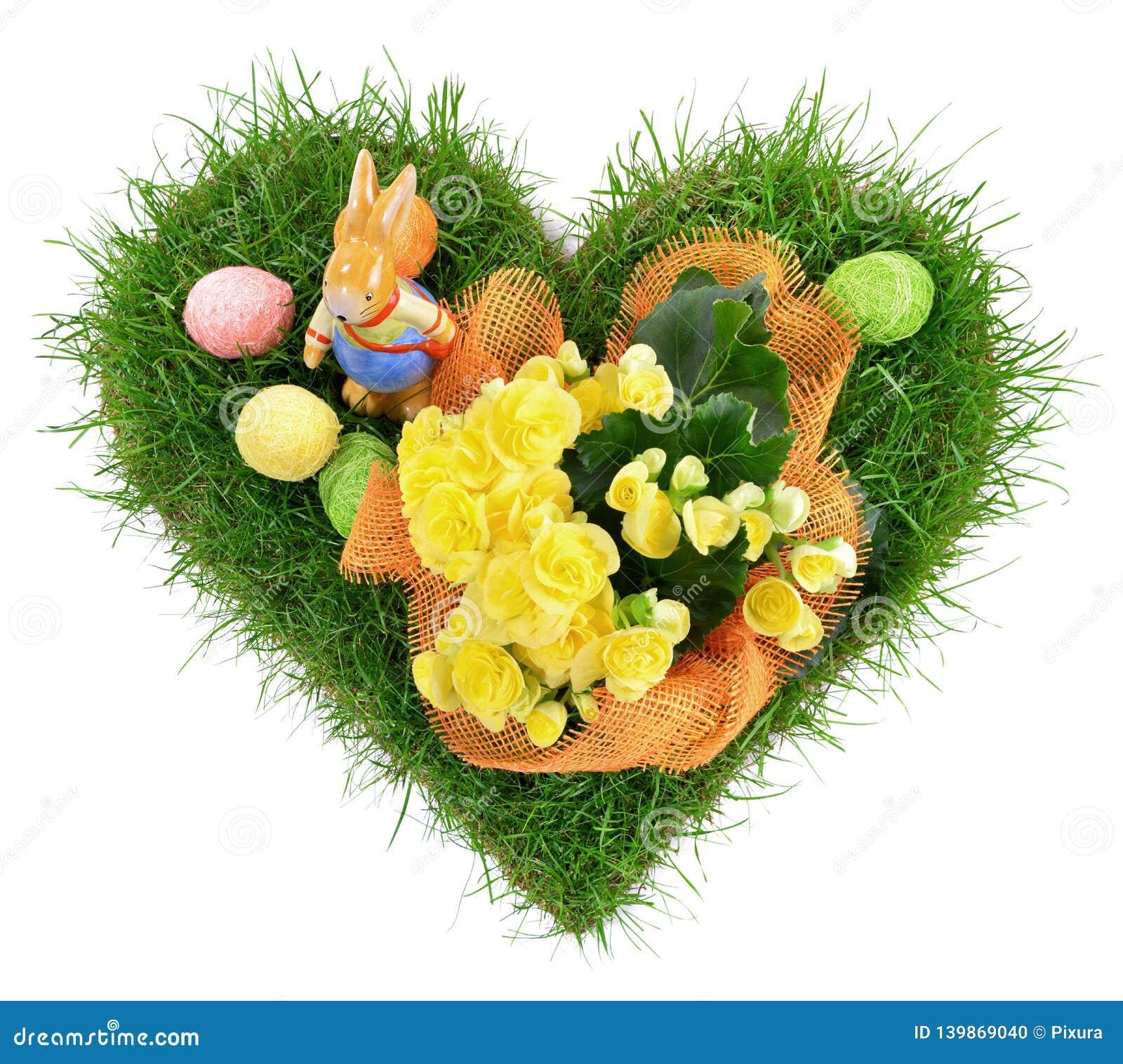 Erba di forma del cuore con le uova di Pasqua su fondo bianco