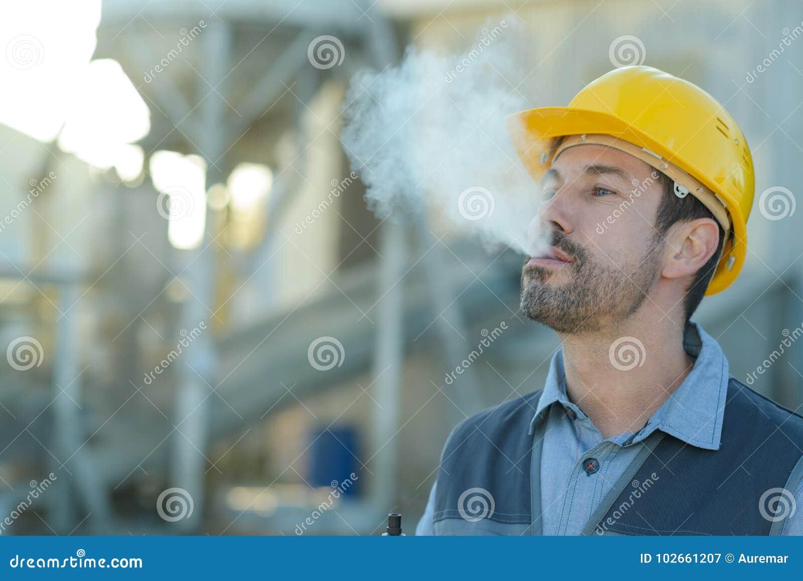 Erbauerarbeitskraft mit Zigarettenrauchbruch