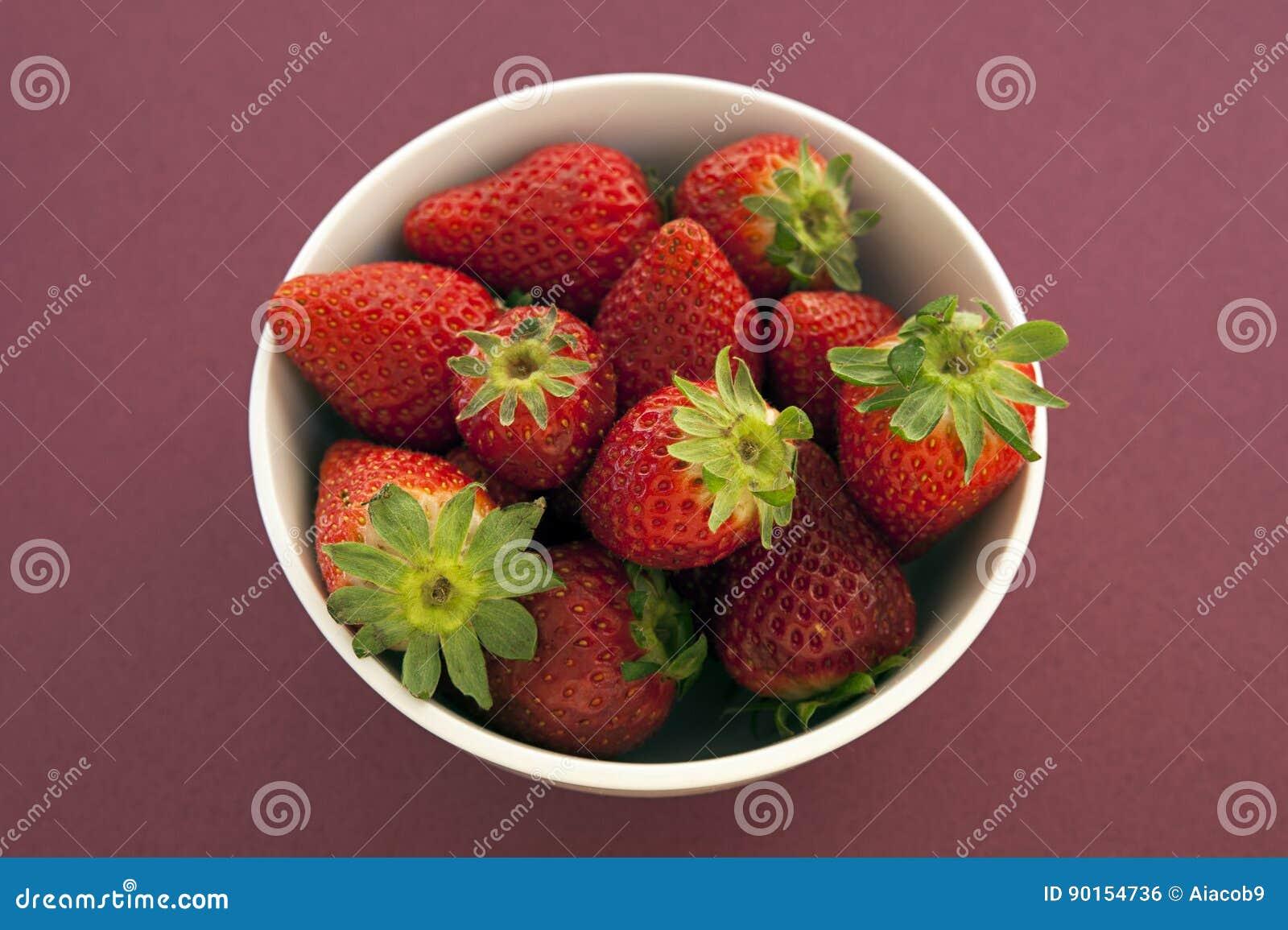 Erdbeeren in einer Schüssel gegen einen festen magentaroten Hintergrund