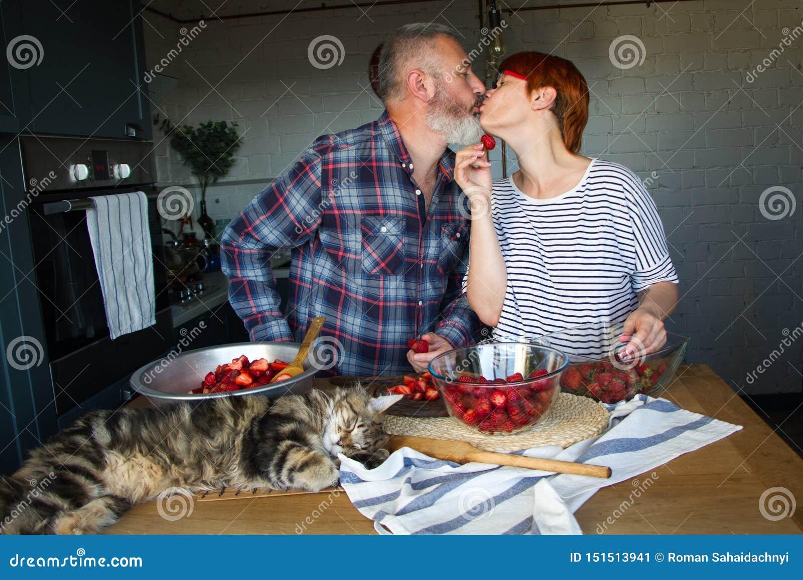 Erdbeeren erwachsener Paarmann und der Frauenschale und -schnittes für Erdbeermarmelade, ziehen sich, Spaß, Maine Coon zu lachen