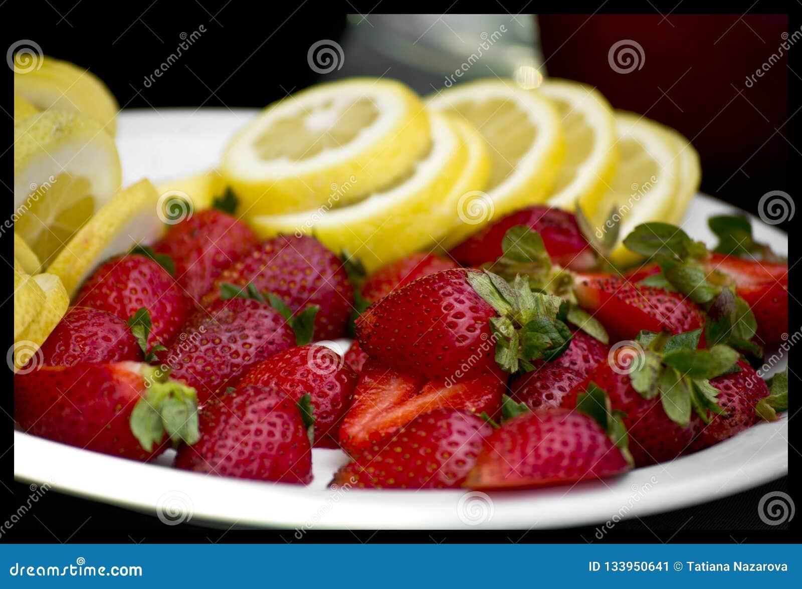Erdbeeren und Zitrone auf einer Platte