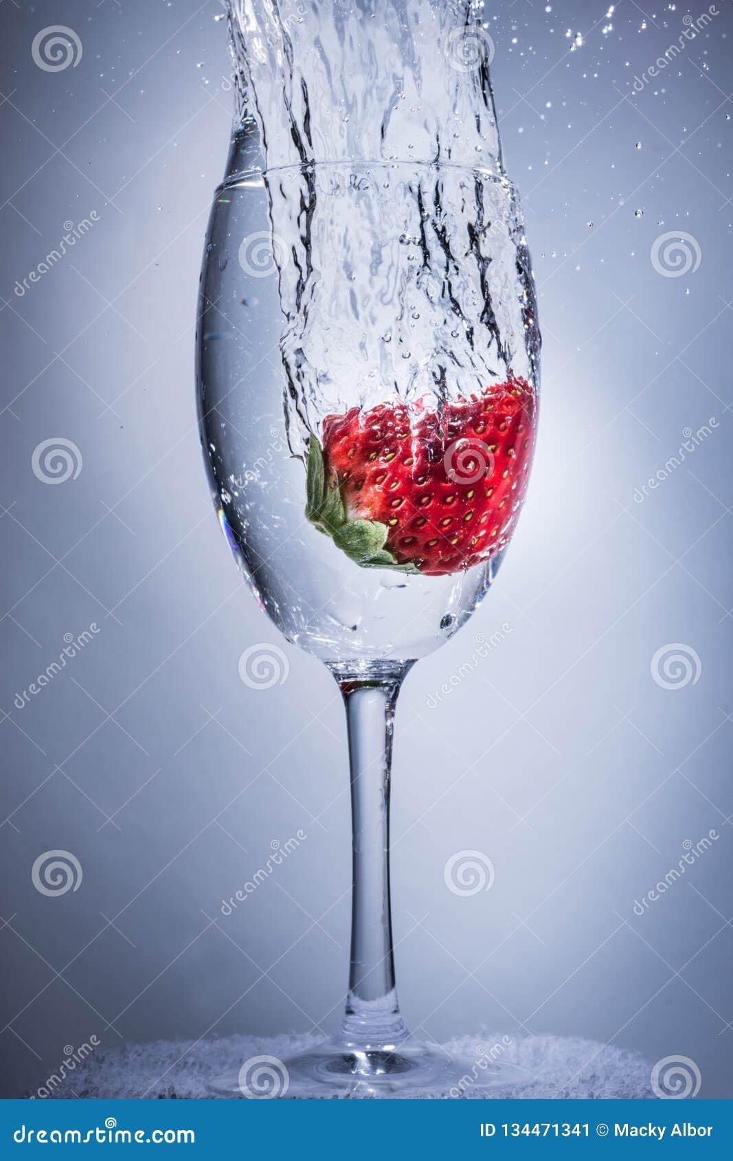 Erdbeerspritzenkopfsprung in Wasser in einem Weinglas
