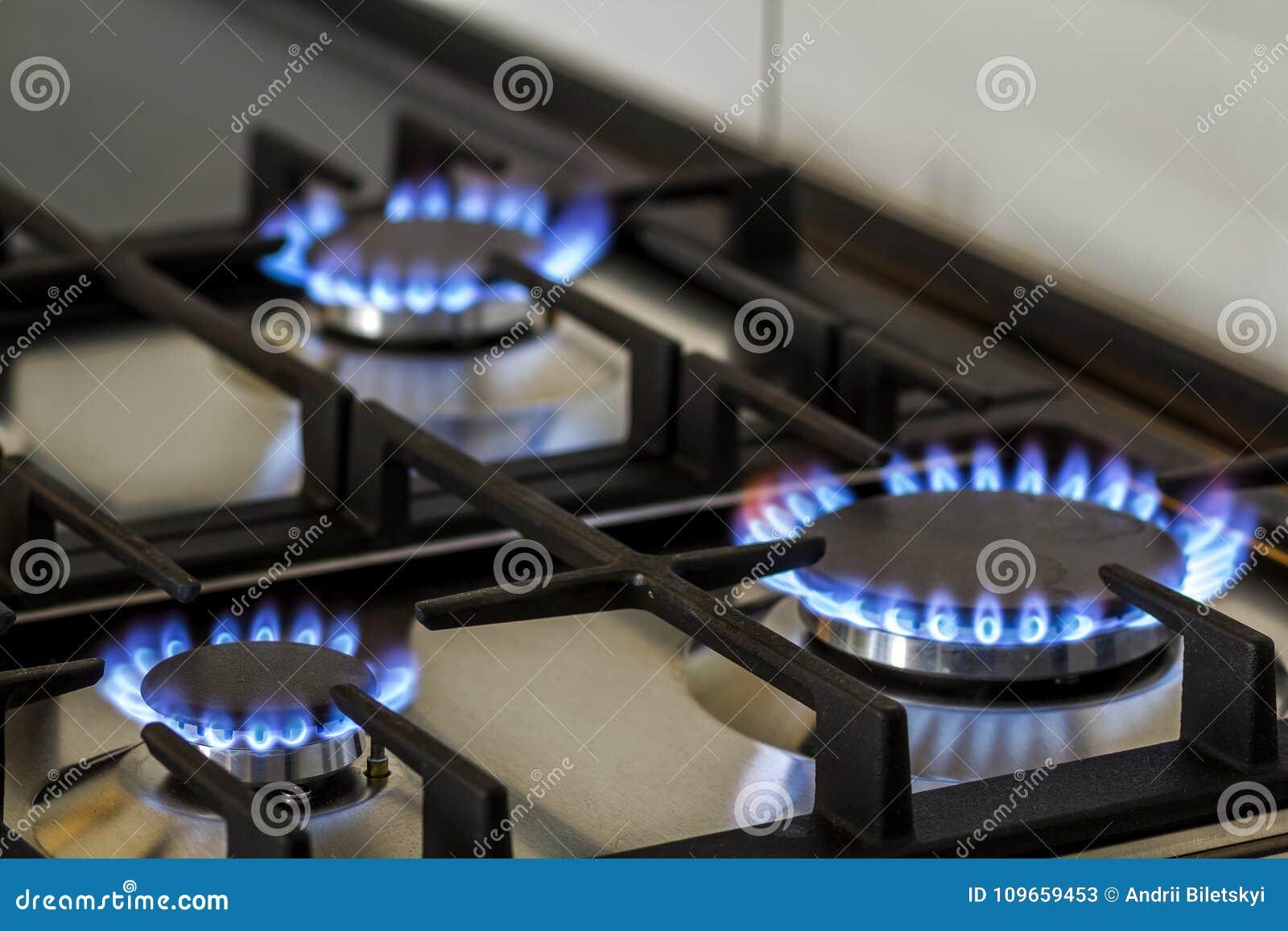 Erdgas, das auf Küchengasherd in der Dunkelheit brennt Platte vom Stahl mit einem Gaskocherbrenner auf einem schwarzen Hintergrun