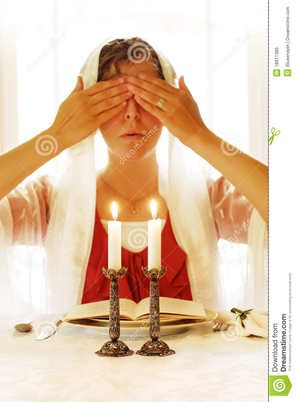 ... blessing for lighting the Shabbat candles. Focus is on candlesticks