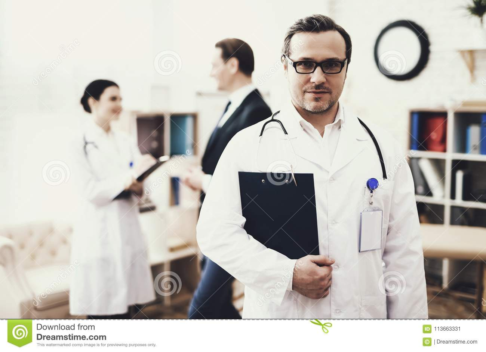 Erfahrener Doktor mit Stethoskop steht mit Ordner von Dokumenten Genesungskonzept