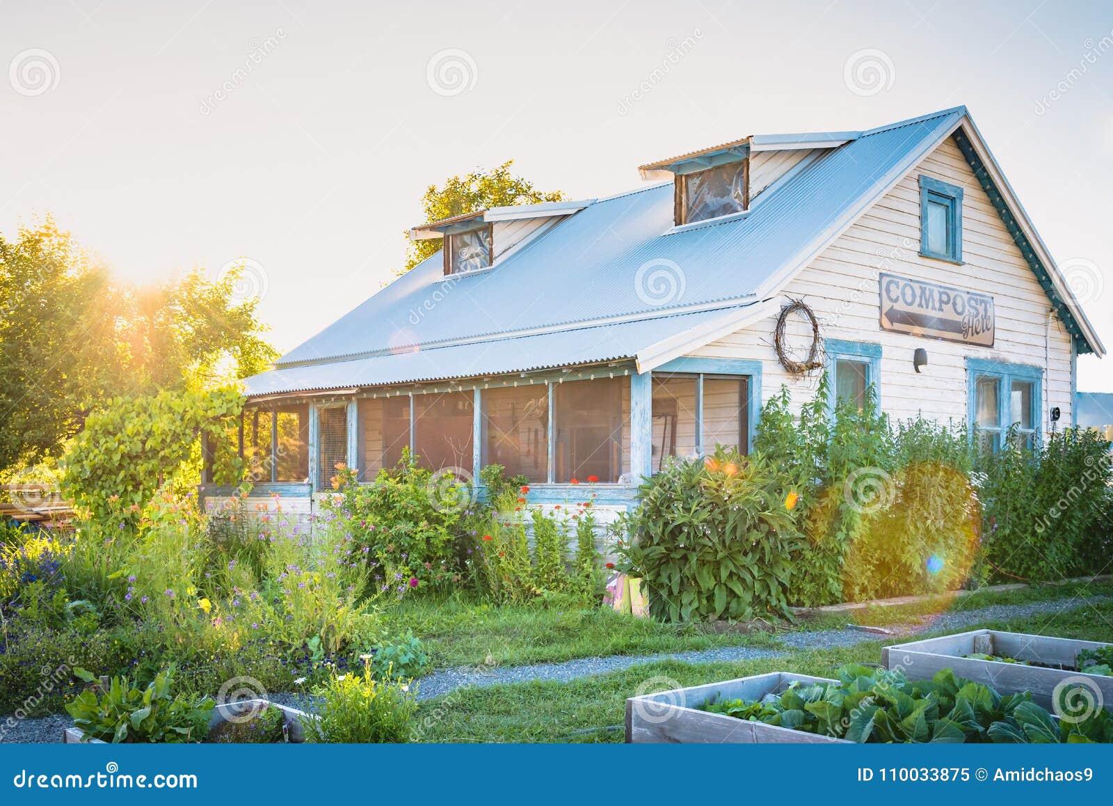 Erfenishuis door bloeiende tuinen bij zonsondergang wordt omringd die