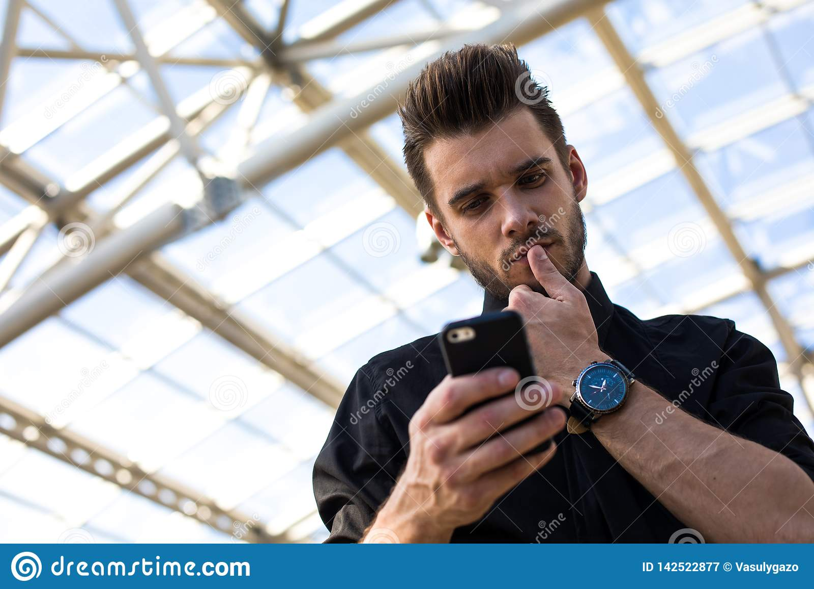 Erfolgreicher männlicher erfahrener Manager unter Verwendung der Anwendungen auf Mobiltelefon während des Arbeitstages