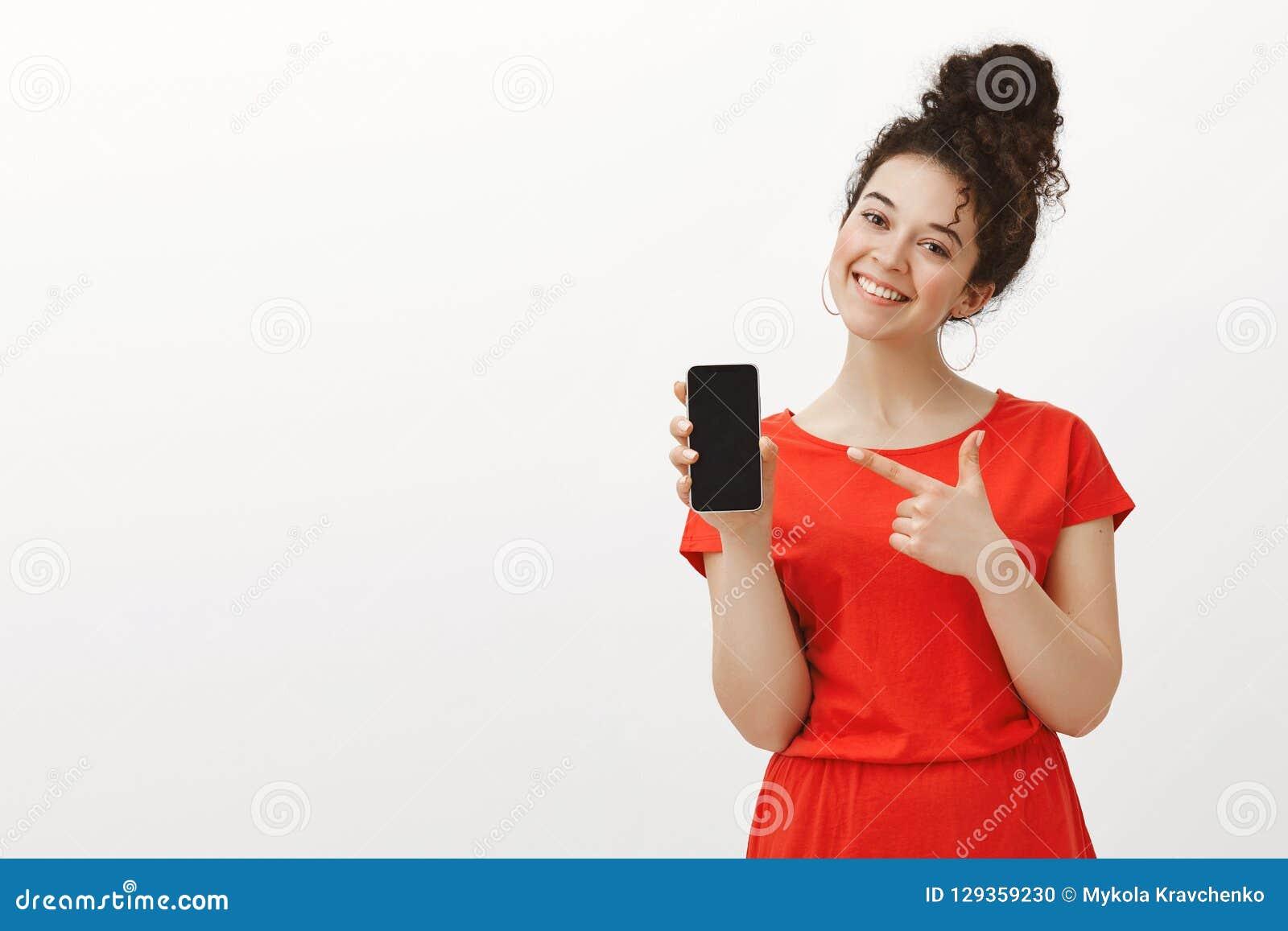 Erfreute sorglose Freundin im netten roten Kleid, Smartphone zeigend und breit lächeln mit gekipptem Kopf beim Zeigen auf